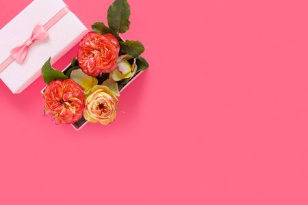 Bouquet of beautiful red roses in gift box on pink background. Copy space for text, invitation or congratulations. Flat lay, top view, copy space concept. 版權商用圖片