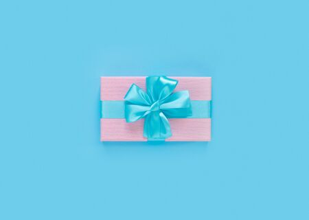 Pink gift box with bow and ribbon on blue paper background with empty place for text. Copy space for text. Flat lay, top view concept.