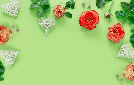 Beautiful red roses with wicker hearts on delicate green paper background.  Creative greeting card.  Flat lay, top view, copy space concept.