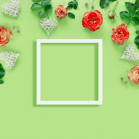 Beautiful red roses with wicker hearts and frame on delicate green paper background.  Creative greeting card. Concept floral pattern.  Flat lay, top view, copy space.