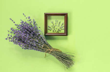 Wooden frames with beautiful bouquet of fragrant lavender in rustic style for gift on green wall. Holiday party decoration. Vintage floral card. Interior concept. Foto de archivo