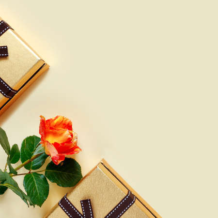 Beautiful pink roses with golden gift box and bow on delicate yellow paper background. Greeting card for Valentine's Day. With place for your text. Flat lay, top view, copy space concept. Foto de archivo