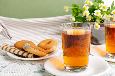 Two cups of hot tea with delicious cookies on white wooden table.