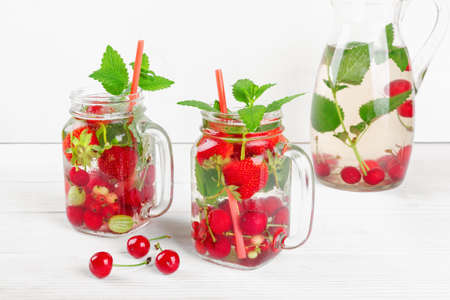 Fresh cool drink of ripe juicy cherry, strawberry, currant and gooseberry berries on white wooden table
