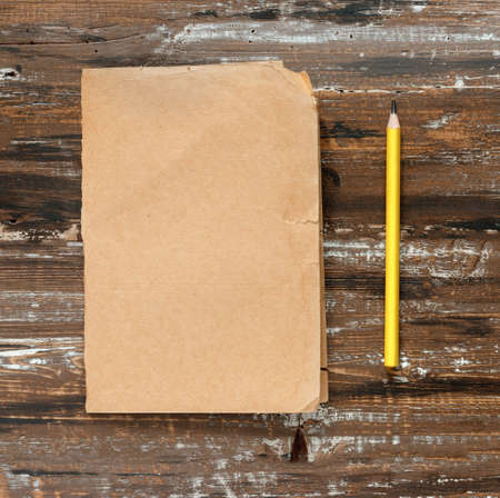 Pencil and sheet of yellow paper for text on wooden background. Flat lay, top view, copy space concept.