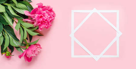 Bouquet of beautiful peonies with paper frame on pink delicate background. Flat lay, top view, copy space creative.