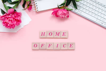 Laptop, accessories and bouquet of beautiful peonies with wooden cubes and text on pink background. Flat lay of working place.