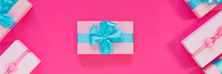 Banner from set of beautiful gift boxes with blue bows on pink background. Holiday sale. Copy space for your text. Flat lay, top view, copy space concept.
