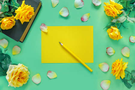 Beautiful bouquet of yellow roses with vintage book and flower petals on green table. Home office and sheet of paper for holiday invitation or congratulations. Flat lay, top view, copy space concept.