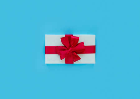 Pink gift box with red bow and ribbon on blue paper background with empty place for text. Copy space for text. Flat lay, top view concept. Foto de archivo