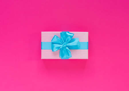 Pink gift box with blue bow and ribbon on paper background with empty place for text. Copy space for text. Flat lay, top view concept.