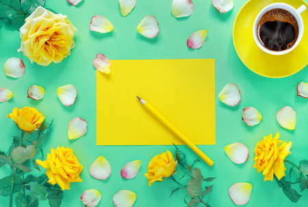 Bouquet of beautiful yellow roses and cup of hot fresh aromatic coffee on green paper background. Notebook sheet and pencil for your text. Flat lay, top view, copy space concept.