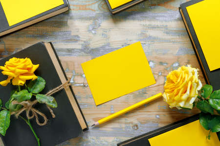 Bouquet of beautiful yellow roses and stack of books on wooden background. Congratulation or invitation to the holiday. Flat lay, top view, copy space concept. Foto de archivo
