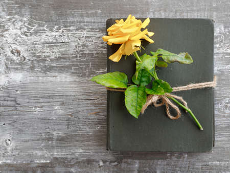 Bouquet of beautiful yellow roses and stack of old vintage books on wooden background. Congratulation or invitation to the holiday. Flat lay, top view, copy space concept.