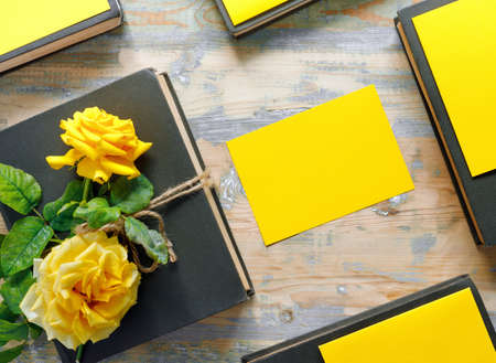 Bouquet of beautiful yellow roses and stack of old vintage books on wooden background. Copy space for nostalgic inscription. Flat lay, top view, copy space concept. Foto de archivo