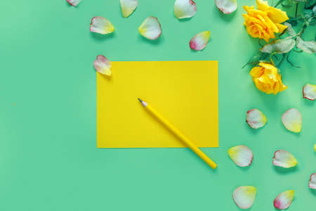 Beautiful bouquet of yellow roses and flower petals on a green table. Notebook and pencil for your text. Flat lay, top view, copy space concept. Foto de archivo