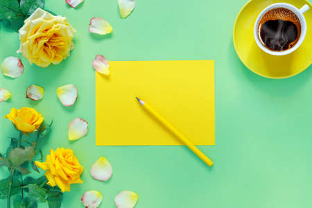 Bouquet of beautiful yellow roses and cup of hot fresh aromatic coffee on green paper background. Notebook sheet and pencil for your text. Flat lay, top view, copy space concept. Foto de archivo - 155115368