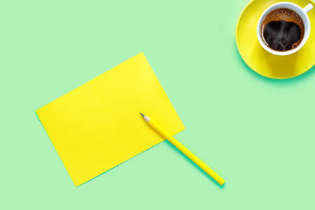 A cup of hot tasty coffee and sheet of yellow paper for notes on green table in the home office. Flat lay, top view, copy space concept.