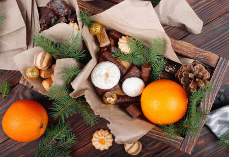 Delicious sweets, chocolates, cookies and oranges for gifts in wooden box on vintage table with fir branches. Top view flat lay group objects Foto de archivo