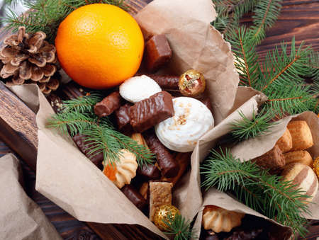 Delicious sweets, chocolates, cookies and oranges for gifts in wooden box on vintage table with fir branches Foto de archivo