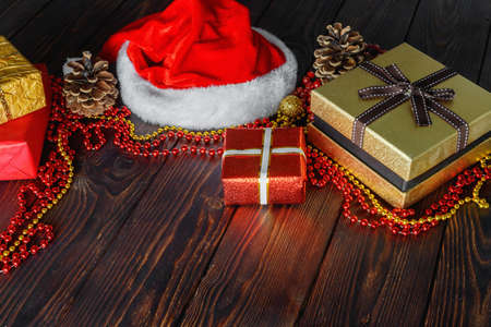 Gift boxes with beads, toys and Santa Claus hat on vintage wooden table in Christmas Foto de archivo - 156853327