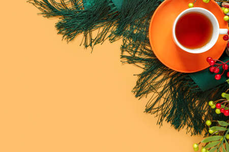 Cup of hot tea, with branches of autumn leaves and warm woolen shawl, on paper background. Creative orange trending background. Flat lay, top view, copy space concept.