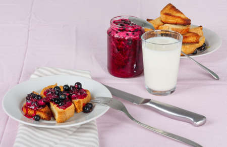 Delicious toasts bread with homemade currant jam with milk on bright crimson tablecloth Foto de archivo