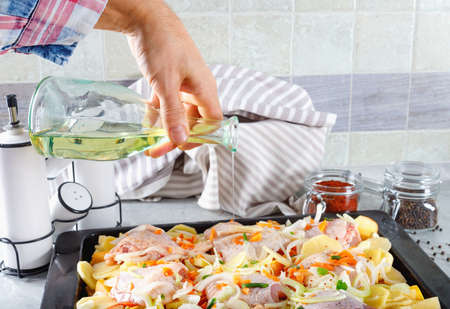 Man pouring olive oil raw chicken with vegetables and spices