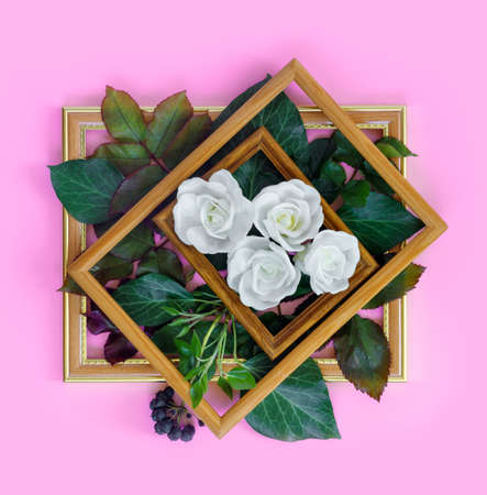 Beautiful white roses with green foliage in vintage wooden frame on bright pink wall for holiday. Creative greeting card. Copy space for your text.