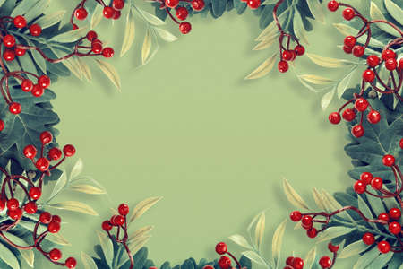 Autumn oak and rowan branches with red berries on green background. Flat lay, top view, copy space concept. Creative paper trending background