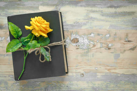 Bouquet of beautiful yellow roses and stack of old vintage books on wooden background. Copy space for nostalgic inscription. Flat lay, top view, copy space concept. Standard-Bild