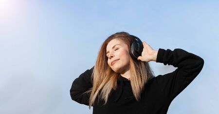 Energy girl with blue headphones listening to music with closed eyes on blue background in studio. She wears black hoody. Long curly hair in tail is flying from moving. Stock fotó