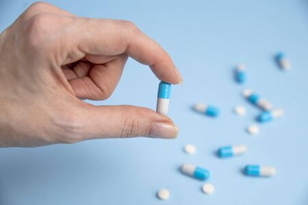 Young Women holding Medicine capsule in a hand on blue background with pills. Concept for Healthcare