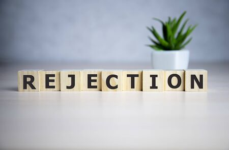 The word REJECTION, spelt with wooden letter tiles over a blue background. Archivio Fotografico