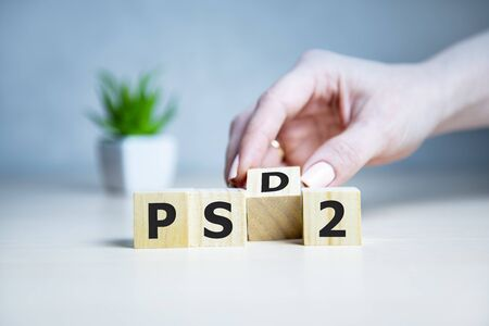 cubes with the message PSD2 - 2nd Payment Services Directive on wooden background. Standard-Bild