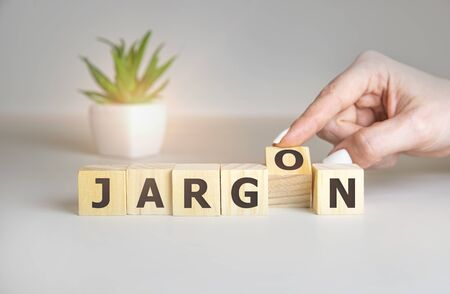 Jargon - hand holding word from wooden blocks with letters, special words and phrases jargon concept, top view on white background