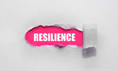 Resilience word concept written under torn paper.