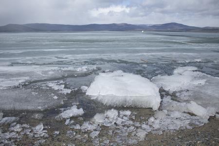 Spring mountain lake with melting ice