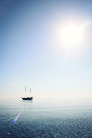 blue sea: Sailing ship profile. Toned image. Sunbeams on the sea surface. Morning sea with boat on the horizon. Aged photo. Calm Sea with a Sailing Vessel. Vertical format. Cirali, Antalya Province, Turkey.