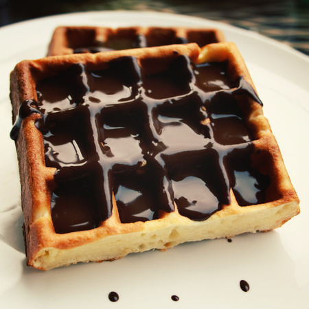 waffle: Chocolate covered Vienna Waffles on the white plate. Vintage photo. Viennese Waffles covered with chocolate topping.