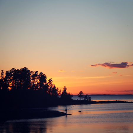 fishman: Sunset on Valaam. Fishman on the bank. Toned photo in vintage style. Nature of island Valaam in Ladoga lake. Russian North. Island of Valaam, Republic of Karelia, Russia. Stock Photo