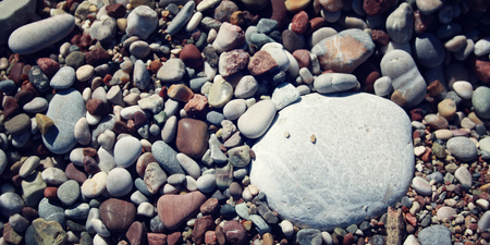amongst: Big round white stone amongst grey and brown pebbles on the beach. Aged image. Copy space for text. Retro filter. Coastline. Turkish beach. Various boulders. Closeup. Wide photo.
