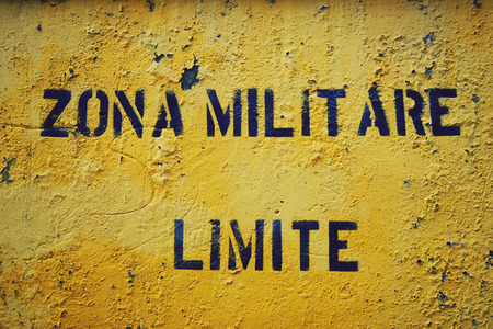 access restricted: Stencil inscription on the yellow painted wall. Restricted access. Yellow sign Zona Militare Limite in italian city Gaeta. Cracked paint on the wall.