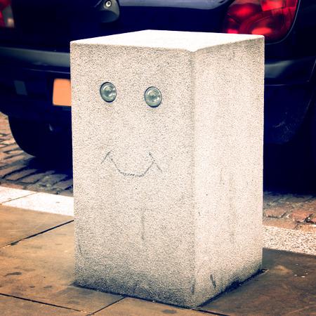 Urban art retro filter. Smiling Parking Stone Pillar - vintage effect. Smiling Road Barricade block - retro photo. London. UK.