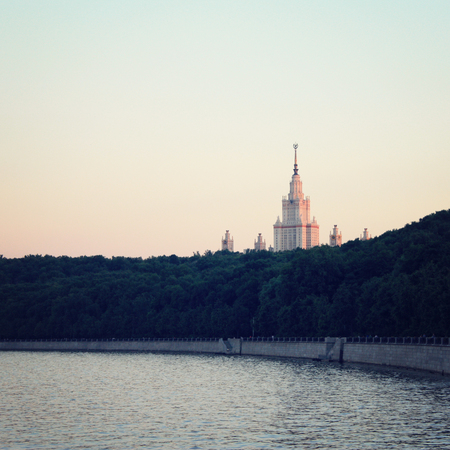 effect sunset: Moscow State University, main building. View from the riverbank. Sunset. Aged photo. Autumn evening in Moscow. Retro effect photo.