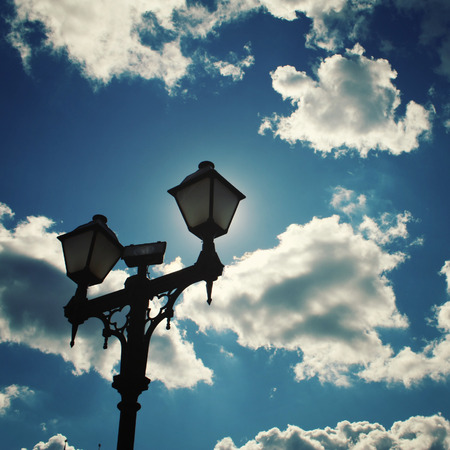 lamp post: Sun hidden by a lamp post. Aged photo. Sun shining behind a street lamp. Vintage effect photo. Tsaritsyno Park, Moscow, Russia.