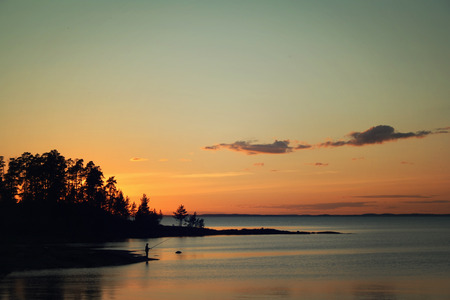 lonesome: Lonesome fisherman on the bank. Russian North. Ladoga lake at sunset. Wild nature. Peaceful Evening. Aged photo in retro style. Summertime. Twilight. Island of Valaam, Karelia, Russia. Stock Photo