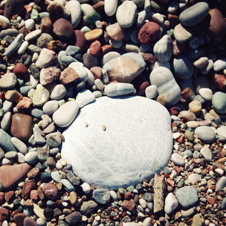 amongst: Big round white stone amongst grey and brown pebbles on the beach. Aged image. Copy space for text. Retro filter. Coastline. Turkish beach. Various boulders. Closeup. Stock Photo