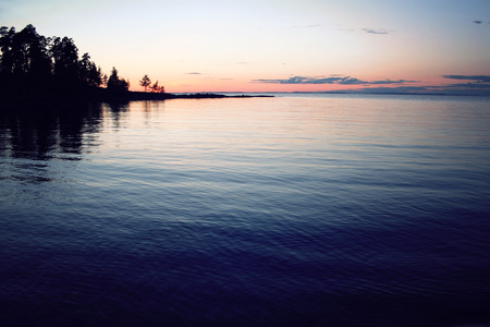 ladoga: Beautiful northern landscape. Russian North. Ladoga lake at sunset. Wild nature. Trees reflected in the water. Aged photo in retro style. Summertime. Twilight. Island of Valaam, Karelia, Russia.