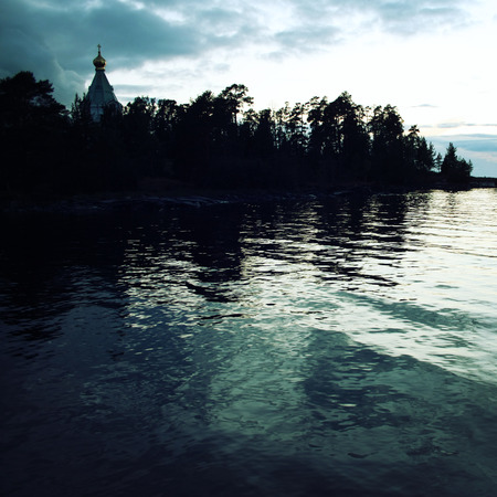 Ladoga lake. Late evening. Saint Nicholass church on the island (skete). Valaam island. Aged photo. Beautiful churches. Nikolsky monastery. Nicholas The Wonderworker church. Karelia, Russia.